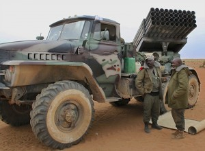 Malian soldiers stand next to a military vehicle in the recently recaptured town of Gao